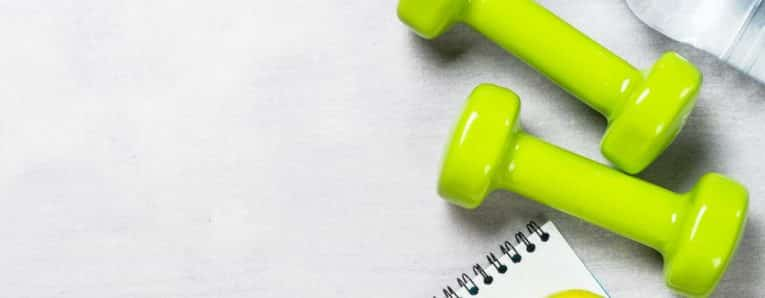 Dumbbells, measuring tape, water and apple with copy space top view. Diet and fitness concept.